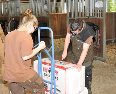 Die Einstreu für die Pferde wird in einer Stallgasse von einer Frau und einem Mann ausgepackt.