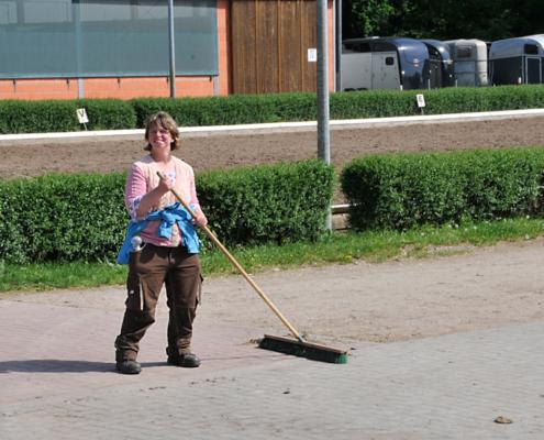 Eine Frau fegt auf dem Hof des Gut Schäferhof