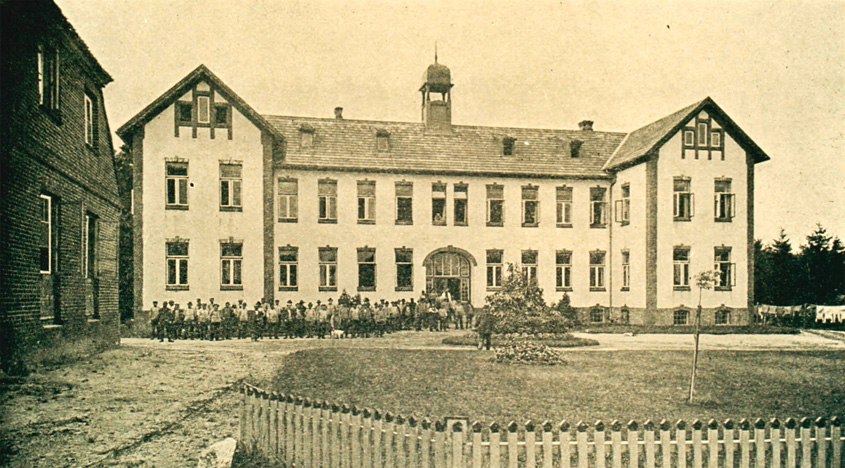Das neue Wohnhaus der Heimatkolonie Schäferhof im Jahr 1904 mit vielen Arbeitern, die davor stehen.